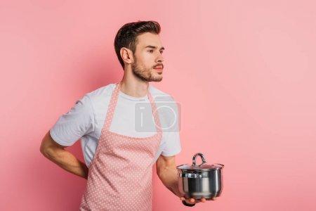 jóképű fiatalember kötényben utánozza pincér, miközben gazdaság csészealj rózsaszín háttér