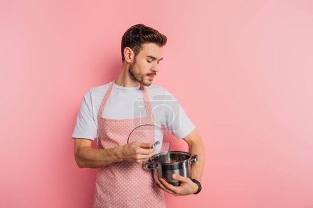 Photo for Serious young man in apron opening and look into saucepan on pink background - Royalty Free Image