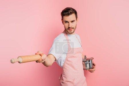 Photo pour Jeune homme concentré dans tablier imitant l'escrime avec casserole et rouleau à pâtisserie sur fond rose - image libre de droit