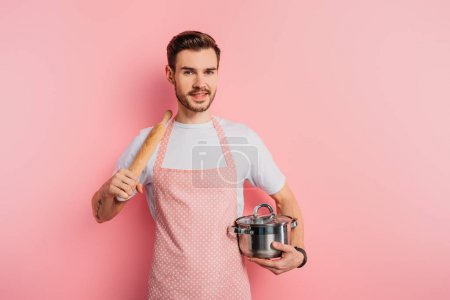 Photo for Cheerful young man in apron holding saucepan and rolling pin on pink background - Royalty Free Image
