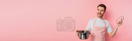 Photo for Panoramic shot of happy young man in apron opening saucepan on pink background - Royalty Free Image