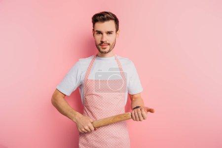 Photo pour Jeune homme confiant sur un tablier tenant un rouleau en bois sur fond rose - image libre de droit