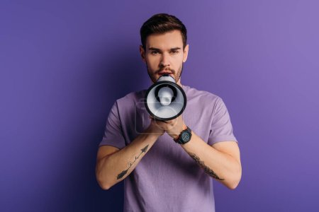 Photo for Handsome young man speaking in megaphone while looking at camera on purple background - Royalty Free Image