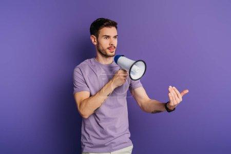 Photo pour Sérieux jeune homme montrant venir ici geste tout en tenant mégaphone sur fond violet - image libre de droit