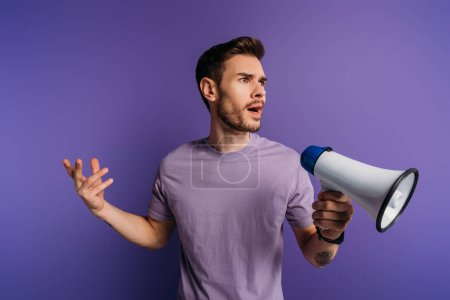 Photo pour Shocked young man holding megaphone and looking away on purple background - image libre de droit