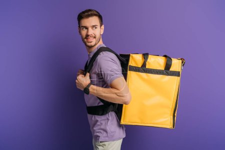 Photo for Cheerful delivery man looking away while carrying thermo backpack on purple background - Royalty Free Image