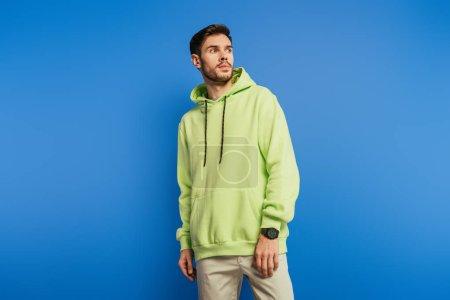 Foto de Handsome serious young man in hoodie looking away on blue background - Imagen libre de derechos