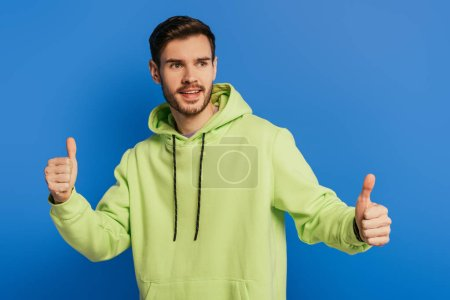 Photo for Excited young man showing thumbs up while looking away isolated on blue - Royalty Free Image