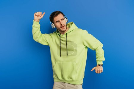 Photo pour Jeune homme excité dans les écouteurs sans fil dansant sur fond bleu - image libre de droit