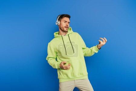 Photo pour Inspiré jeune homme dans des écouteurs sans fil imitant jouer de la guitare isolée sur bleu - image libre de droit