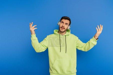 Photo pour Jeune homme inspiré dans des écouteurs sans fil debout avec les mains levées isolé sur bleu - image libre de droit