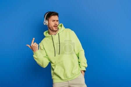 Photo pour Jeune homme excité dans les écouteurs sans fil chantant avec les yeux fermés sur fond bleu - image libre de droit