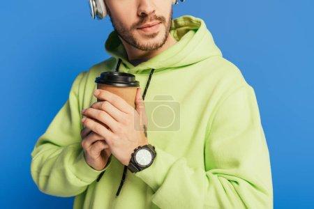 abgeschnittene Ansicht eines jungen Mannes mit drahtlosen Kopfhörern, der Kaffee to go auf blauem Grund hält