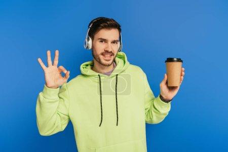 glücklicher junger Mann mit drahtlosen Kopfhörern, Kaffee to go in der Hand und Ok-Zeichen auf blauem Grund