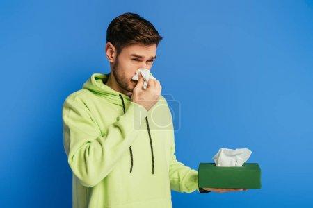 Photo pour Malade jeune homme essuyant nez avec serviette en papier sur fond bleu - image libre de droit