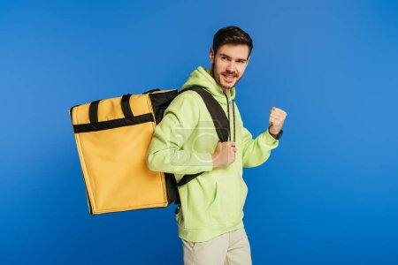 Photo for Happy delivery man showing winner gesture while carrying thermo backpack isolated on blue - Royalty Free Image