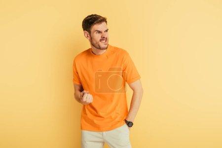 Photo pour Un homme en colère grimace et fait un geste menaçant en regardant ailleurs sur un fond jaune - image libre de droit