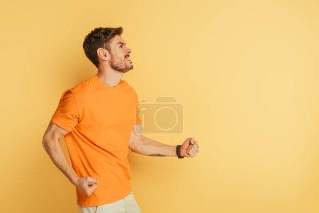 Photo pour Un jeune homme irrité qui fait des gestes menaçants et grimace en regardant sur fond jaune - image libre de droit