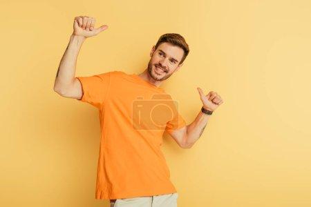 Foto de Feliz hombre guapo mostrando los pulgares hacia arriba mientras mira hacia otro lado en el fondo amarillo - Imagen libre de derechos