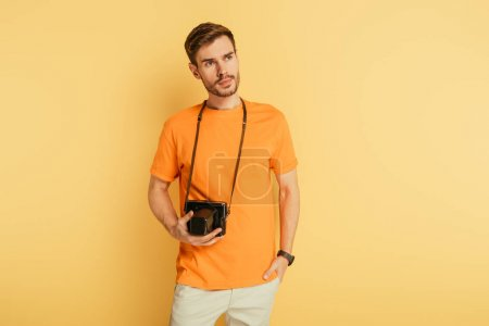 Photo for Handsome thoughtful photographer with digital camera holding hand in pocket and looking away on yellow background - Royalty Free Image