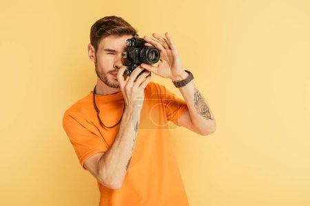 Photo pour Beau photographe attentif prenant des photos avec appareil photo numérique isolé sur jaune - image libre de droit