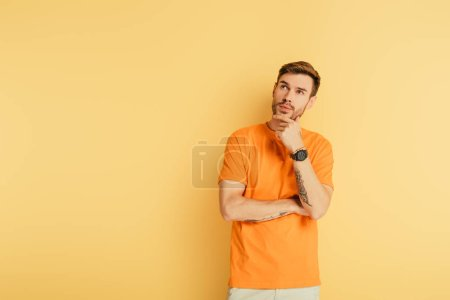 Photo for Thoughtful young man touching chin and looking up isolated on yellow - Royalty Free Image
