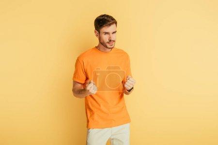 Photo pour Mécontent, jeune homme irrité montrant les poings tout en regardant la caméra sur fond jaune - image libre de droit