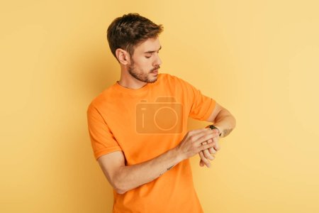 Photo for Serious young man looking at wristwatch on yellow background - Royalty Free Image
