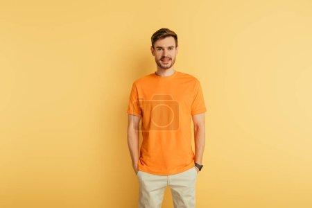 Photo pour Jeune homme souriant en t-shirt orange debout avec les mains dans les poches sur fond jaune - image libre de droit