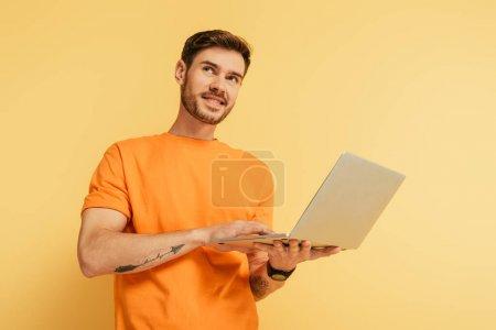 Photo pour Homme rêveur souriant regardant loin tout en tenant ordinateur portable sur fond jaune - image libre de droit