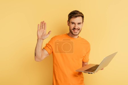 Photo pour Heureux homme agitant la main à la caméra tout en tenant ordinateur portable sur fond jaune - image libre de droit