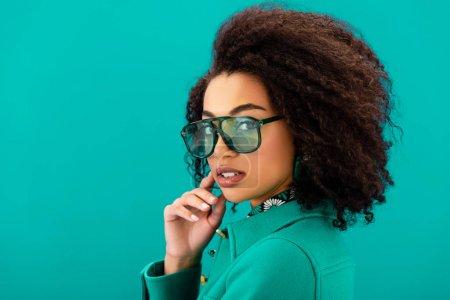 Photo pour Femme afro-américaine élégante en veste regardant caméra isolée sur turquoise - image libre de droit