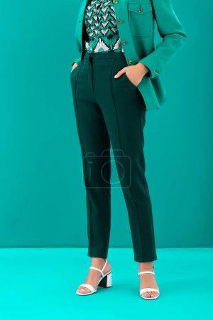 Photo pour Vue recadrée de femme afro-américaine avec les mains dans les poches sur fond turquoise - image libre de droit