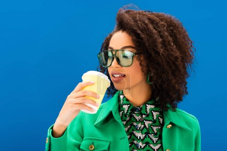 Photo for Stylish african american woman drinking coffee isolated on blue - Royalty Free Image