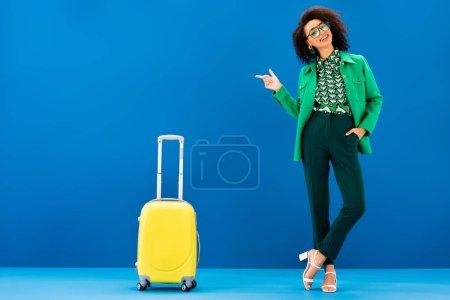 Photo pour Femme afro-américaine souriante pointant du doigt et se tenant près du sac de voyage sur fond bleu - image libre de droit