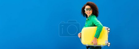 Photo for Panoramic shot of smiling african american woman holding travel bag isolated on blue - Royalty Free Image