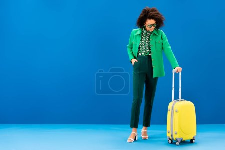 Photo for Smiling african american woman looking at travel bag on blue background - Royalty Free Image