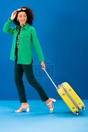 Photo for Smiling african american woman walking with travel bag on blue background - Royalty Free Image