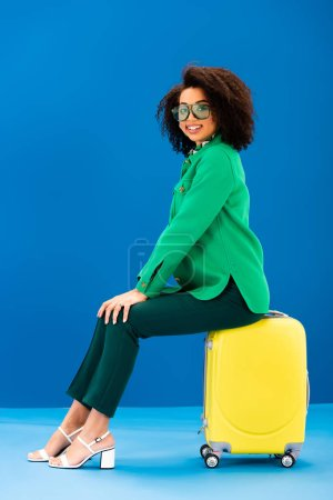 Photo for Smiling african american woman sitting on travel bag on blue background - Royalty Free Image