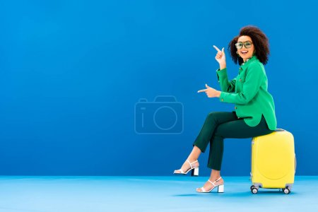 smiling african american woman pointing with fingers and sitting on travel bag on blue background