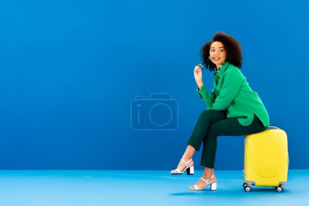 Photo pour Femme afro-américaine souriante tenant des lunettes de soleil et assise sur un sac de voyage sur fond bleu - image libre de droit