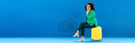 Photo pour Plan panoramique de femme afro-américaine choquée assise sur un sac de voyage sur fond bleu - image libre de droit