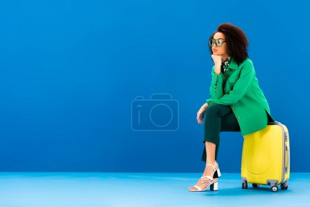 pensive african american woman sitting on travel bag on blue background