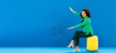 Photo for Panoramic shot of smiling african american woman sitting on travel bag and pointing with hands on blue background - Royalty Free Image