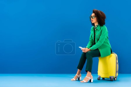 Photo for Shocked african american woman sitting on travel bag and holding smartphone on blue background - Royalty Free Image