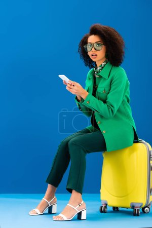 shocked african american woman sitting on travel bag and holding smartphone on blue background