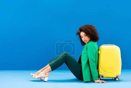 Photo pour Élégante femme afro-américaine assise près du sac de voyage sur fond bleu - image libre de droit