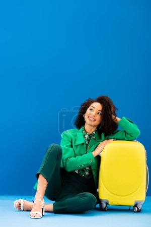 smiling african american woman sitting near travel bag on blue background