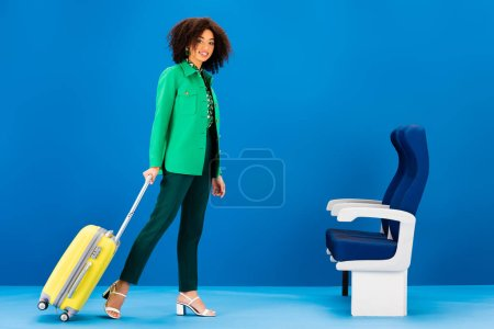 Photo for Smiling african american woman holding travel bag on blue background - Royalty Free Image