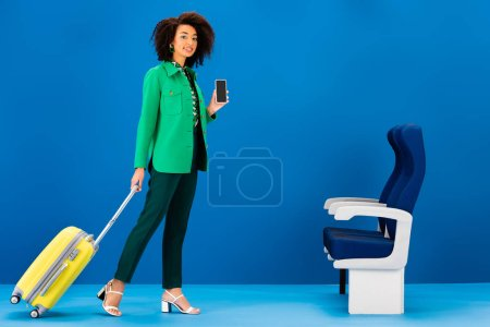 smiling african american woman holding travel bag and smartphone on blue background